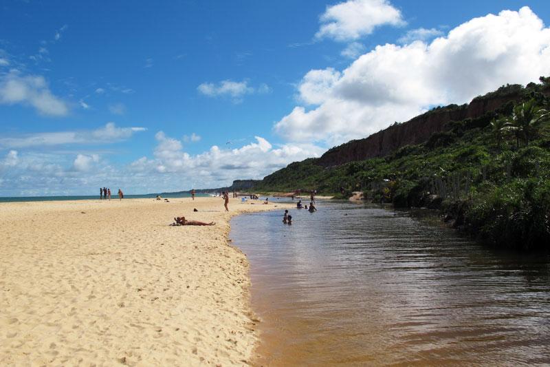 Rio que encontra o mar na praia de Pitinga