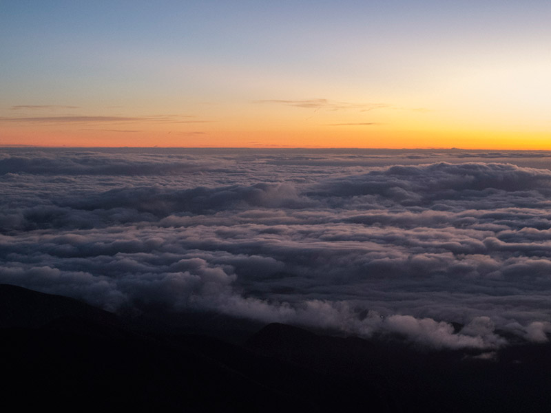 Vista do Pico da Bandeira no nascer do sol, cheio de nuvens